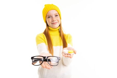 European attractive red-haired girl holds out glasses and lenses on a white background.