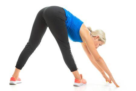 Europäisches blondes Mädchen führt körperliche Übungen auf weißem Hintergrund durch.