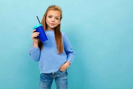 portrait of a european girl drinking holding a glass on a light blue wall. Stok Fotoğraf