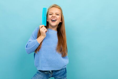 smiling european girl holding a hair comb on a light blue background with copyspace.