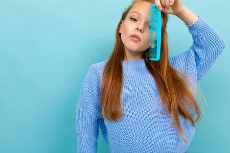 beautiful european girl holding a hair comb on a light blue background. Zdjęcie Seryjne