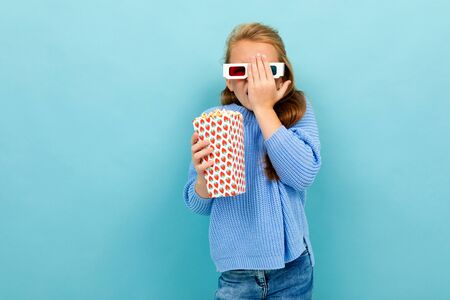 attractive girl in movie glasses is holding popcorn in her hands on a light blue wall.