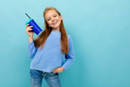 attractive european girl holding a glass in her hands on a light blue background. Stok Fotoğraf
