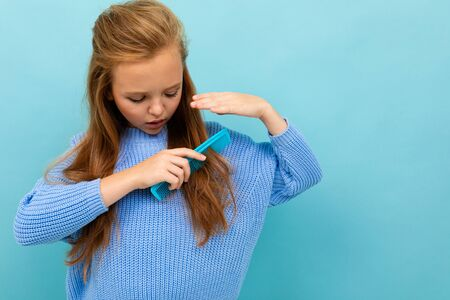 cute european girl combing her hair on a light blue background.