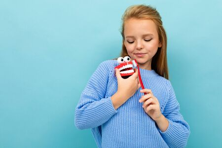 attractive european girl holds a toothbrush and jaw in her hands on a light blue wall with copyspace. Stockfoto