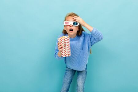 surprised girl in movie glasses is holding popcorn in her hands on a light blue background.