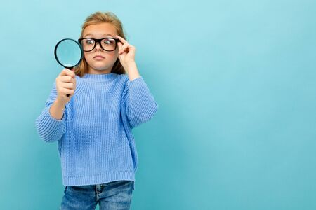 surprised european girl in glasses looks through a magnifying glass on a light blue wall with copyspace.