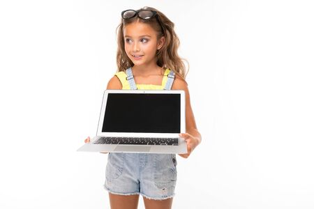 attractive european girl with glasses holding a computer in her hands with mockup on a light blue wall. Stock fotó