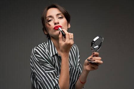 Happy caucasian woman do makeup with brushes a isolated on grey background. Imagens - 134796460