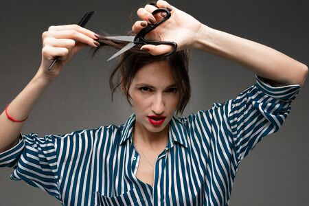Happy caucasian woman do haircut on phone camera isolated on grey background. Zdjęcie Seryjne