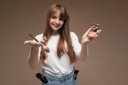 Caucasian teenager do makeup with brushes and smiles isolated on brown background. Zdjęcie Seryjne