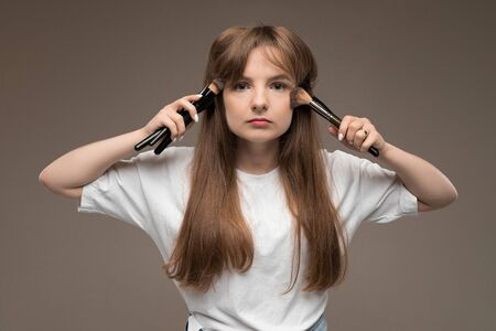 Caucasian teenager do makeup with brushes isolated on brown background.