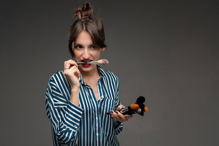 Happy caucasian woman with makeup brushes isolated on grey background. Zdjęcie Seryjne