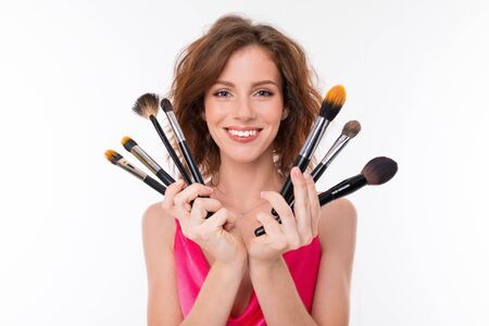 Young beautiful girl show her makeup brushes isolated on white background. Imagens - 134796522