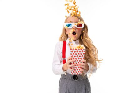 surprised european girl in movie glasses with popcorn in hands on a white wall. Stock Photo