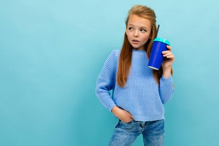 portrait of a stylish european girl drinking holding a glass on a light blue wall with copyspace.