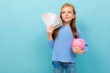 attractive european girl holding a piggy bank and money in hands on a light blue background. Reklamní fotografie