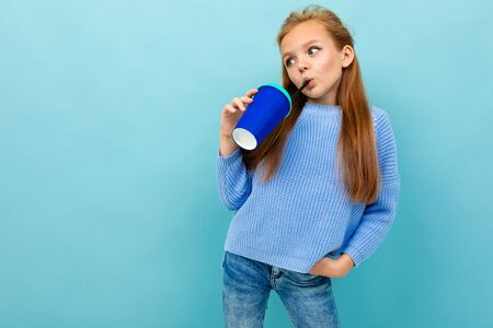 attractive european girl is drinking something from a glass on a light blue wall with copyspace. Stock Photo