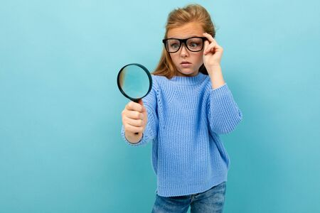 curious european girl in glasses looks through a magnifying glass on a light blue background.