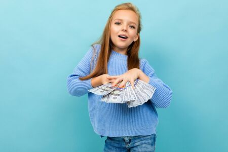 attractive european girl throws money in hands on a light blue background. Stock Photo