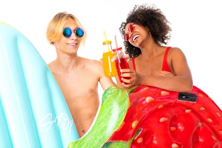 attractive couple european guy and african girl in swimsuits drink cocktails and hold swimming mattresses. Stock Photo