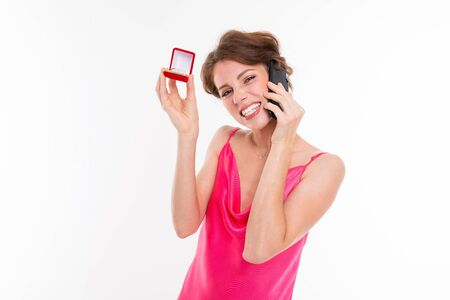 Young beautiful girl holds a box for a engagement ring and call the phone someone isolated on white background.