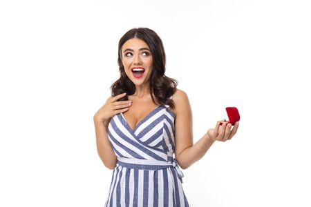 surprised girl with brown hair in a dress with a neckline holds a box with an engagement ring on a white background.
