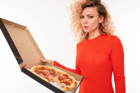 european curly blond girl in a red dress holds a box of pizza on a white studio wall. Banco de Imagens