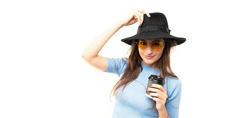 Brunette model with yellow sunglasses and hat drinks coffe and posing for the camera on white background.