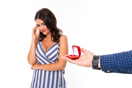 girl looks at a ring in a box by which a man makes a marriage proposal on a white background.