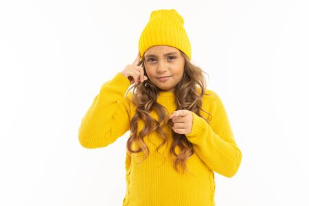 European attractive girl in a yellow hat twists at the temple on a white background.