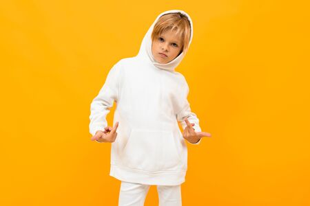 attractive blond boy in a white sweater with a hood on an orange background with copy space.
