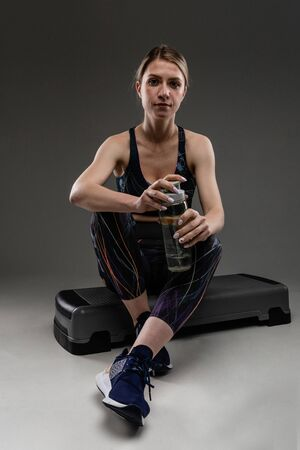 Sport woman sits with bottle of water after training. Stock Photo