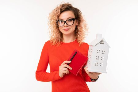 attractive girl in glasses with a notebook and a mock up of a house on a white background.