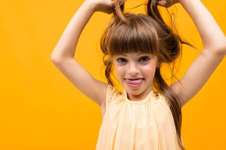 girl grimaces and twists her hair on an orange background.