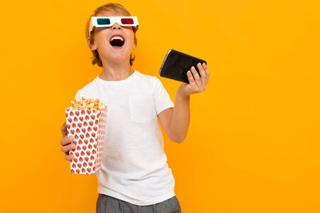 surprised boy in glasses for a movie theater with popcorn and a phone on a yellow background.