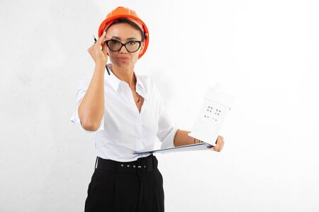 handsome girl builder in a white classic shirt with orange construction helmet with documents on a white background. Stock fotó