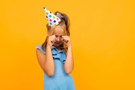 girl with a holiday cap on her head cries on an orange background.