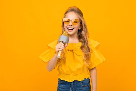 Nice little girl with her glasses sings songs into the microphone isolated on white background.