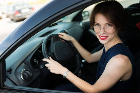 Caucasian woman in strict style of clothing, red lips, short haircut gets out of the car for an important meeting in the office, goes for an interview