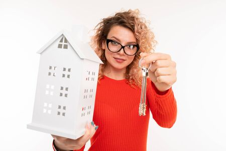 realtor girl holds out keys and a house model on a white background.