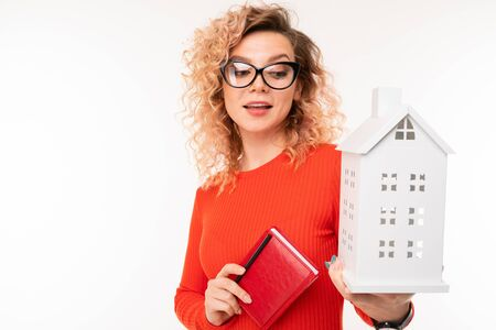 european girl in glasses with a notebook and a mock up of a house on a white background. Stock fotó