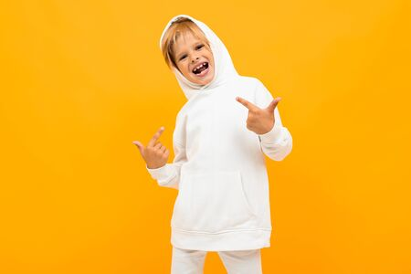attractive blond boy in a white sweater is grimacing on an yellow background. Фото со стока