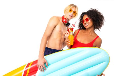 Pretty african female and caucasian blonde man stands in swimsuit with rubber beach mattresses, drinks juice and smiles, isolated on white background.
