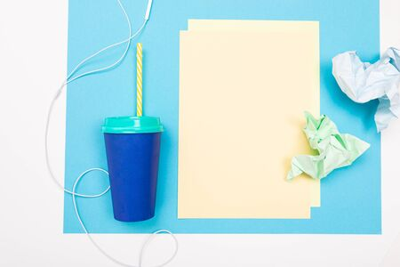 School and office supplies such as note, pens, pencils, calculator, brush, scissors, coffee, laptop lie neatly on a white and blue background