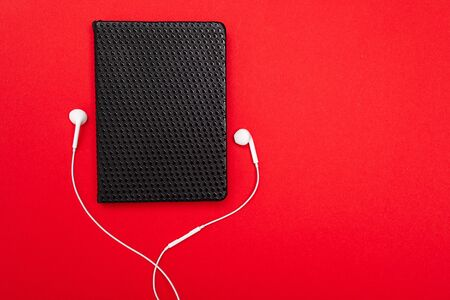 Black notebook with white earphones isolated on red background.