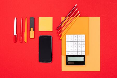 School and office supplies such as note, pens, pencils, calculator, brush, scissors, coffee, laptop lie neatly on a red background Imagens