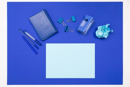 School and office supplies such as note, pens, pencils and other lie neatly on a blue background Imagens - 135442290