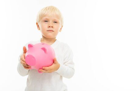 Little blonde caucasian boy with pink pig moneybox isolated on white background. Banco de Imagens