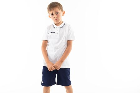 sad offended boy with bangs in a white t-shirt on a white background with copy space.